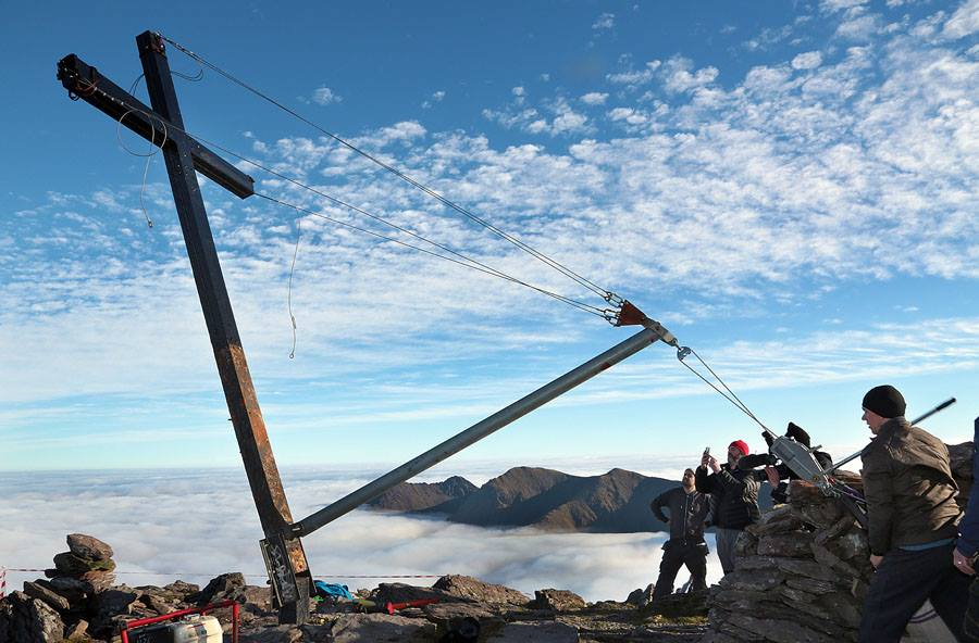 KerryClimbing guide - Piaras yanks the lever to re-erect the summit cross on Carrauntoohil after vandals cut it down in 2014